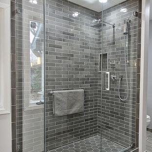 Ejemplo de cuarto de baño principal, minimalista, de tamaño medio, con armarios con paneles lisos, puertas de armario grises, ducha esquinera, sanitario de dos piezas, baldosas y/o azulejos grises, baldosas y/o azulejos de cerámica, paredes grises, suelo de baldosas de porcelana, lavabo bajoencimera y encimera de cuarzo compacto