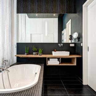 Kleines Modernes Badezimmer En Suite mit offenen Schränken, braunen Schränken, Einbaubadewanne, schwarzer Wandfarbe, Aufsatzwaschbecken, Waschtisch aus Holz, schwarzem Boden und brauner Waschtischplatte in Berlin
