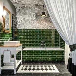Неиссякаемый источник вдохновения для домашнего уюта: главная ванная комната среднего размера в классическом стиле с фасадами с утопленной филенкой, белыми фасадами, накладной ванной, душем над ванной, зеленой плиткой, плиткой кабанчик, серыми стенами, настольной раковиной, столешницей из дерева, черным полом и коричневой столешницей