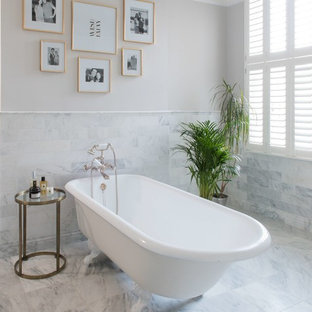 Medium sized contemporary bathroom in London with a freestanding bath, grey tiles, white tiles, marble tiles, beige walls, marble flooring and grey floors.