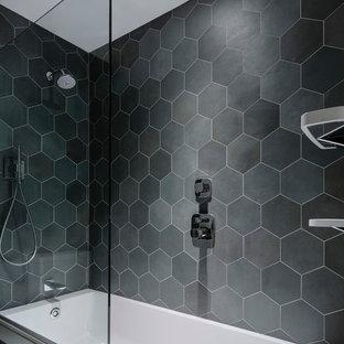 Imagen de cuarto de baño minimalista con bañera empotrada, combinación de ducha y bañera, baldosas y/o azulejos negros, baldosas y/o azulejos grises, baldosas y/o azulejos de cerámica y paredes negras
