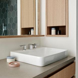 Idee per una stanza da bagno padronale minimalista di medie dimensioni con ante lisce, ante in legno chiaro, vasca ad alcova, vasca/doccia, WC monopezzo, piastrelle nere, piastrelle grigie, piastrelle in ceramica, pareti bianche, lavabo a bacinella e top in cemento