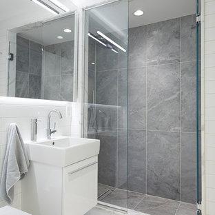 Foto di una stanza da bagno padronale minimalista con ante lisce, ante bianche, doccia alcova, WC sospeso, piastrelle bianche, piastrelle in ceramica, pareti blu, pavimento alla veneziana, lavabo sospeso, pavimento bianco e porta doccia a battente