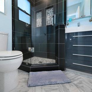 Ispirazione per una piccola stanza da bagno padronale moderna con ante con riquadro incassato, ante grigie, lavabo a consolle, top in superficie solida, doccia ad angolo, WC a due pezzi, piastrelle grigie, piastrelle in gres porcellanato, pareti blu e pavimento in marmo