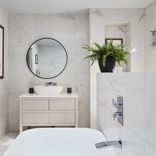 This is an example of a coastal bathroom in London with flat-panel cabinets, beige cabinets, a freestanding bath, white tiles, a vessel sink, white floors and white worktops.