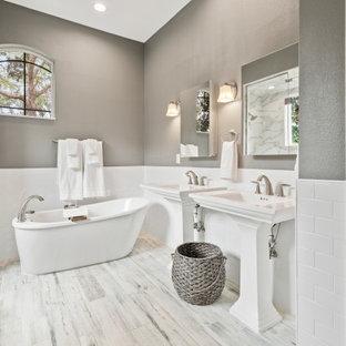 Klassisk inredning av ett en-suite badrum, med ett fristående badkar, en toalettstol med hel cisternkåpa, vit kakel, grå väggar, ett piedestal handfat och grått golv