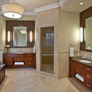На фото: огромная главная ванная комната в классическом стиле с угловым душем, врезной раковиной, фасадами с утопленной филенкой, фасадами цвета дерева среднего тона, столешницей из известняка, полновстраиваемой ванной, раздельным унитазом, бежевой плиткой, каменной плиткой, бежевыми стенами и мраморным полом