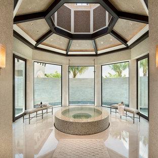 Exempel på ett medelhavsstil en-suite badrum, med en jacuzzi, beige väggar, kalkstensgolv, beige kakel och beiget golv