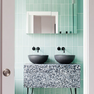 Example of a mid-sized trendy green tile and ceramic tile multicolored floor bathroom design in London with a vessel sink and green walls