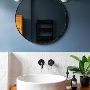 Cette image montre une petit salle de bain bohème pour enfant avec un placard à porte persienne, des portes de placard marrons, une baignoire posée, un espace douche bain, un WC suspendu, un carrelage blanc, des carreaux de porcelaine, un mur bleu, un sol en carrelage de porcelaine, un plan de toilette en bois, un sol noir, un plan de toilette marron, meuble simple vasque, meuble-lavabo sur pied et un plafond en bois.
