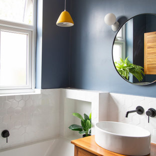 Inspiration for a small bohemian bathroom in London with louvered cabinets, brown cabinets, a built-in bath, a wall mounted toilet, white tiles, porcelain tiles, blue walls, porcelain flooring, wooden worktops, black floors, brown worktops, a single sink, a freestanding vanity unit and a wood ceiling.