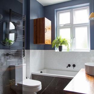 Inspiration för ett litet eklektiskt brun brunt badrum för barn, med luckor med lamellpanel, bruna skåp, ett platsbyggt badkar, våtrum, en vägghängd toalettstol, vit kakel, porslinskakel, blå väggar, klinkergolv i porslin, träbänkskiva och svart golv