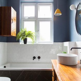 Cette image montre une petit salle de bain principale traditionnelle avec un placard à porte persienne, des portes de placard marrons, une baignoire posée, un espace douche bain, un WC suspendu, un carrelage blanc, des carreaux de porcelaine, un mur bleu, un sol en carrelage de porcelaine, un plan de toilette en bois, un sol noir, un plan de toilette marron, meuble simple vasque, meuble-lavabo sur pied et un plafond en bois.