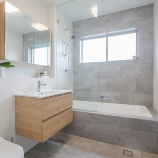 Inspiration för ett litet funkis badrum, med släta luckor, skåp i ljust trä, ett platsbyggt badkar, en dusch/badkar-kombination, grå kakel, keramikplattor, bänkskiva i kvarts, en toalettstol med separat cisternkåpa, vita väggar, klinkergolv i keramik och ett nedsänkt handfat