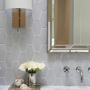 Ispirazione per una piccola stanza da bagno padronale moderna con lavabo sottopiano, ante lisce, ante in legno bruno, top in marmo, vasca sottopiano, doccia ad angolo, WC sospeso, piastrelle grigie, piastrelle in ceramica, pareti grigie e pavimento in gres porcellanato