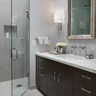 Idee per una piccola stanza da bagno padronale moderna con lavabo sottopiano, ante lisce, ante in legno bruno, top in marmo, vasca sottopiano, doccia aperta, WC sospeso, piastrelle grigie, piastrelle in ceramica, pareti grigie e pavimento in gres porcellanato