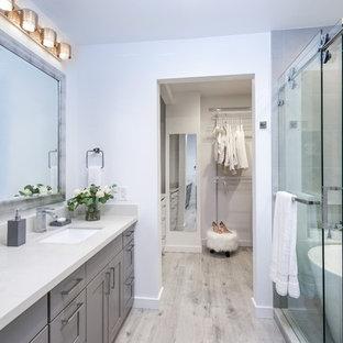 Ispirazione per una grande stanza da bagno padronale classica con ante lisce, ante grigie, vasca freestanding, doccia aperta, WC monopezzo, piastrelle bianche, lastra di pietra, pareti blu, parquet chiaro, lavabo da incasso e top in superficie solida