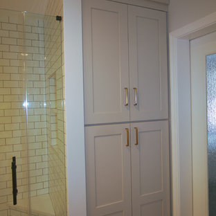 Inspiration for a small transitional 3/4 white tile and subway tile marble floor and gray floor bathroom remodel in Philadelphia with shaker cabinets, gray cabinets, a two-piece toilet, white walls, an integrated sink, quartzite countertops, a hinged shower door and white countertops