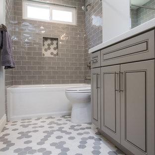 Modelo de cuarto de baño infantil, tradicional renovado, pequeño, con armarios con paneles con relieve, puertas de armario grises, bañera empotrada, combinación de ducha y bañera, sanitario de una pieza, baldosas y/o azulejos grises, baldosas y/o azulejos de cemento, paredes grises, suelo con mosaicos de baldosas, lavabo bajoencimera, encimera de cuarzo compacto, suelo gris y ducha con cortina