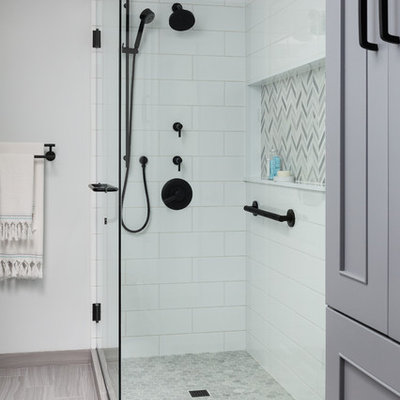 Corner shower - mid-sized modern master white tile and ceramic tile porcelain tile and gray floor corner shower idea in Seattle with recessed-panel cabinets, gray cabinets, a one-piece toilet, blue walls, an undermount sink, quartz countertops, a hinged shower door and white countertops