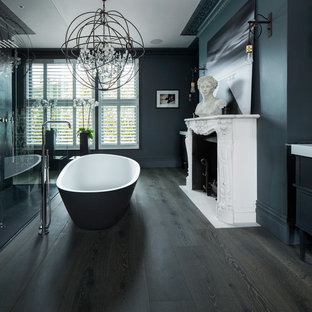 Photo of a classic bathroom in London with a freestanding bath, blue walls and dark hardwood flooring.