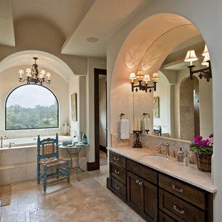 Idee per un'ampia stanza da bagno padronale mediterranea con lavabo sottopiano, ante in stile shaker, ante in legno bruno, vasca da incasso, WC monopezzo, piastrelle beige, piastrelle di vetro, pareti bianche e pavimento in travertino