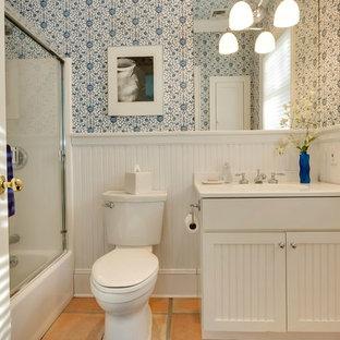 Foto di una stanza da bagno con doccia tradizionale di medie dimensioni con ante a persiana, ante bianche, vasca ad alcova, vasca/doccia, WC a due pezzi, pareti bianche, lavabo integrato, top in superficie solida, porta doccia scorrevole, pavimento in terracotta e pavimento rosso