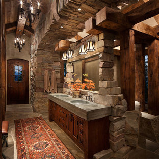 Large mountain style master stone tile slate floor bathroom photo in Other with raised-panel cabinets, dark wood cabinets, brown walls, an integrated sink and solid surface countertops