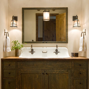 Example of a mountain style bathroom design in Other with beige walls, a trough sink, shaker cabinets and dark wood cabinets