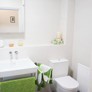 Small contemporary family bathroom in London with a built-in bath, white tiles, ceramic tiles, white walls, lino flooring, a wall-mounted sink, tiled worktops and a two-piece toilet.
