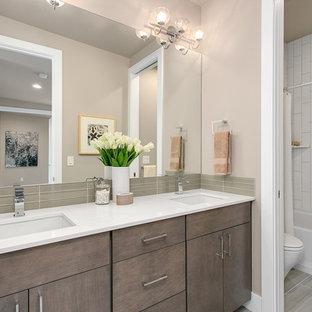 Bild på ett mellanstort funkis badrum, med släta luckor, skåp i mellenmörkt trä, en dusch/badkar-kombination, grå kakel, glaskakel, grå väggar, klinkergolv i porslin, ett undermonterad handfat och bänkskiva i kvarts