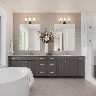 Diseño de cuarto de baño principal, de estilo americano, grande, con armarios con paneles empotrados, puertas de armario grises, bañera exenta, ducha empotrada, baldosas y/o azulejos grises, baldosas y/o azulejos de porcelana, paredes grises, suelo de baldosas de porcelana, lavabo bajoencimera, encimera de cuarzo compacto, suelo gris, ducha con puerta con bisagras y encimeras blancas