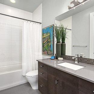 Idee per una grande stanza da bagno design con lavabo sottopiano, ante in stile shaker, ante in legno bruno, top in quarzite, vasca/doccia, WC a due pezzi, piastrelle nere, piastrelle di vetro e pareti grigie