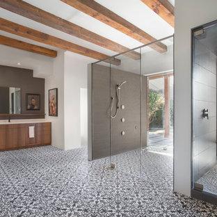Immagine di una grande stanza da bagno padronale moderna con ante lisce, ante in legno scuro, top in superficie solida, piastrelle di cemento, doccia a filo pavimento, pareti bianche, pavimento in cementine, lavabo sottopiano, pavimento multicolore e porta doccia a battente