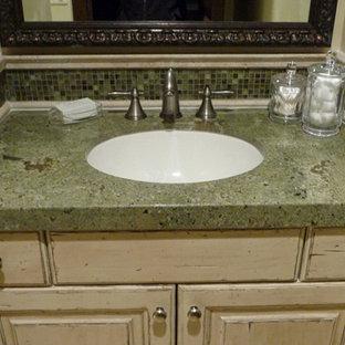 Imagen de cuarto de baño clásico, pequeño, con lavabo bajoencimera, puertas de armario con efecto envejecido, encimera de granito, baldosas y/o azulejos verdes, paredes beige, armarios con paneles con relieve, baldosas y/o azulejos en mosaico y encimeras verdes
