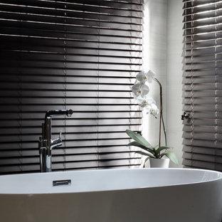 ニューヨークの中サイズのコンテンポラリースタイルのおしゃれなマスターバスルーム (ガラス扉のキャビネット、濃色木目調キャビネット、置き型浴槽、段差なし、一体型トイレ、ベージュのタイル、セラミックタイル、ベージュの壁、セラミックタイルの床、一体型シンク、クオーツストーンの洗面台、ベージュの床、開き戸のシャワー、ベージュのカウンター) の写真