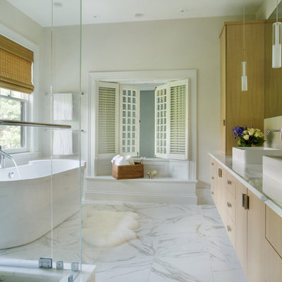 Example of a trendy marble floor and gray floor freestanding bathtub design in Boston with a vessel sink