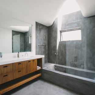 Tub/shower combo - modern concrete floor tub/shower combo idea in Los Angeles with flat-panel cabinets, medium tone wood cabinets and white countertops