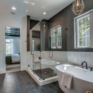Modelo de cuarto de baño principal, contemporáneo, grande, con armarios con paneles lisos, puertas de armario de madera clara, bañera exenta, ducha esquinera, baldosas y/o azulejos blancas y negros, paredes blancas, lavabo bajoencimera, suelo negro, ducha con puerta con bisagras y encimeras negras
