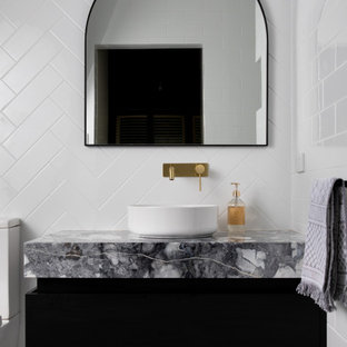 Contemporary bathroom in Adelaide with ceramic tile, marble benchtops, flat-panel cabinets, black cabinets, white tile, a vessel sink and grey benchtops.