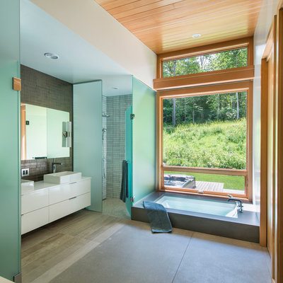 Inspiration for a mid-sized contemporary master gray tile and ceramic tile concrete floor bathroom remodel in Burlington with white cabinets, white walls, flat-panel cabinets, a one-piece toilet, a vessel sink and quartz countertops