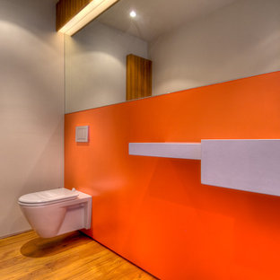 ロサンゼルスのモダンスタイルのおしゃれな浴室 (壁付け型シンク、壁掛け式トイレ、オレンジの壁) の写真