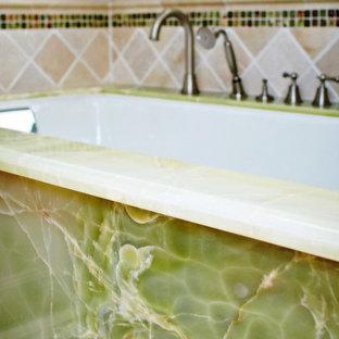 Foto de cuarto de baño principal, clásico, de tamaño medio, con armarios con rebordes decorativos, puertas de armario de madera en tonos medios, bañera encastrada sin remate, paredes grises, lavabo bajoencimera, encimera de ónix y encimeras verdes