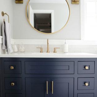 ニューヨークの中くらいのモダンスタイルのおしゃれなサウナ (シェーカースタイル扉のキャビネット、青いキャビネット、グレーの壁、磁器タイルの床、クオーツストーンの洗面台、白い洗面カウンター、アンダーカウンター洗面器) の写真