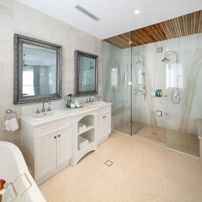Example of a classic master beige tile and marble tile marble floor and beige floor freestanding bathtub design in Sydney with recessed-panel cabinets, white cabinets, quartz countertops and white countertops