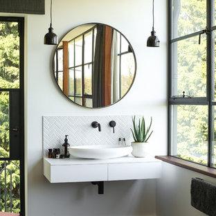 ロンドンの中サイズのエクレクティックスタイルのおしゃれなマスターバスルーム (オープンシェルフ、置き型浴槽、アルコーブ型シャワー、壁掛け式トイレ、白いタイル、磁器タイル、グレーの壁、濃色無垢フローリング、壁付け型シンク、珪岩の洗面台、茶色い床、開き戸のシャワー、白い洗面カウンター) の写真