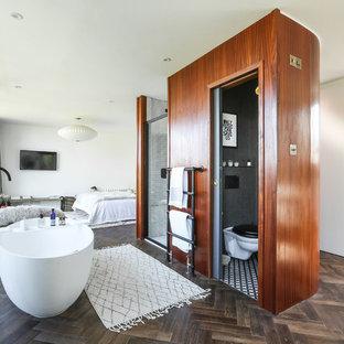 Modelo de cuarto de baño principal, contemporáneo, de tamaño medio, con armarios abiertos, bañera exenta, ducha empotrada, sanitario de pared, baldosas y/o azulejos blancos, baldosas y/o azulejos de porcelana, paredes grises, suelo de madera oscura, lavabo suspendido, encimera de cuarcita, suelo marrón, ducha con puerta con bisagras y encimeras blancas