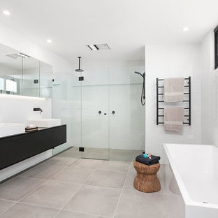 Photo of a contemporary master bathroom in Sydney with black cabinets, a freestanding tub, a one-piece toilet, white tile, ceramic tile, white walls, ceramic floors, a vessel sink, solid surface benchtops, grey floor, a hinged shower door, black benchtops, flat-panel cabinets and an alcove shower.