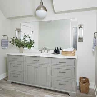 Стильный дизайн: большая главная ванная комната в стиле кантри с фасадами островного типа, серыми фасадами, душем в нише, раздельным унитазом, серой плиткой, керамогранитной плиткой, белыми стенами, паркетным полом среднего тона, врезной раковиной, столешницей из искусственного кварца, серым полом, душем с распашными дверями, белой столешницей, унитазом, тумбой под одну раковину, напольной тумбой и сводчатым потолком - последний тренд