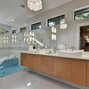 Bathroom - mid-sized contemporary master blue tile and glass tile ceramic tile and gray floor bathroom idea in Austin with flat-panel cabinets, medium tone wood cabinets, a one-piece toilet, gray walls, a vessel sink, solid surface countertops and white countertops